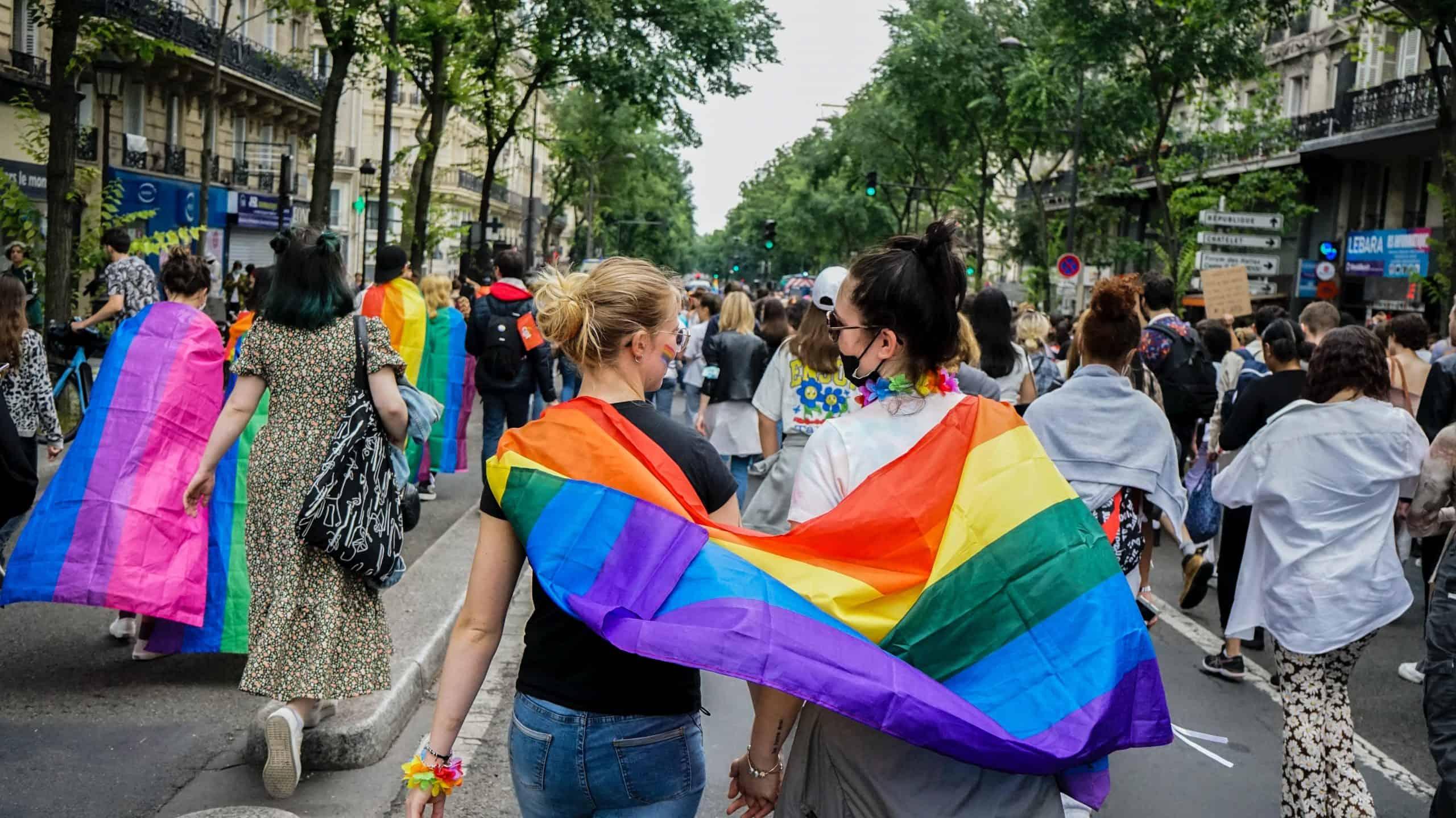 Lesbian couple walking with a rainbow flag.