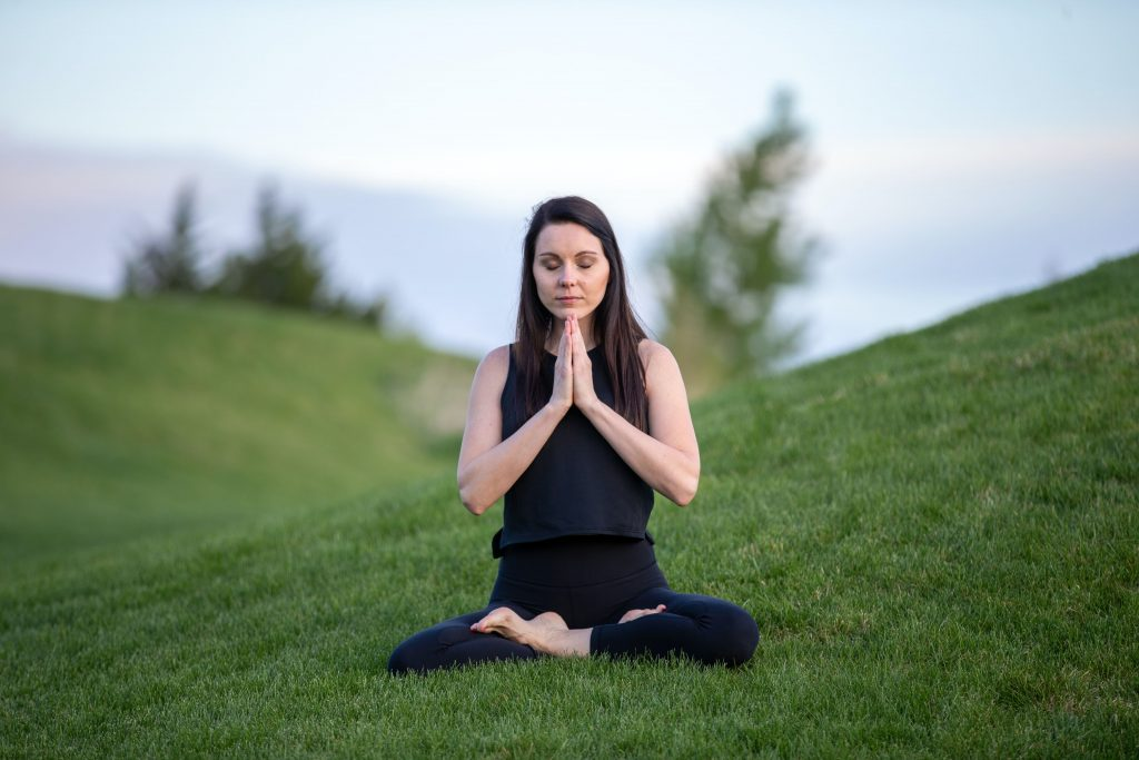 Woman meditating in a field.