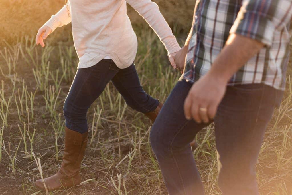 Catholic couple walking in a field.